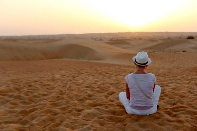 Incentive Travel Event In Dubai - woman sits in contemplation in desert